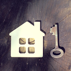 retro home/ layout of a small house with a chimney and a window and an old iron key on a wooden surface