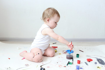 happy little 1 year baby girl painting at home