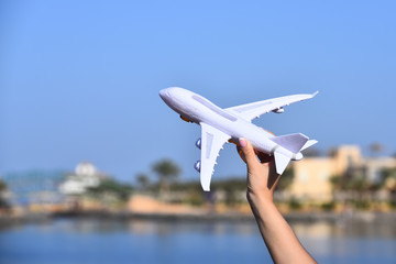 Flying transport white airplane in female hand on natural landscape