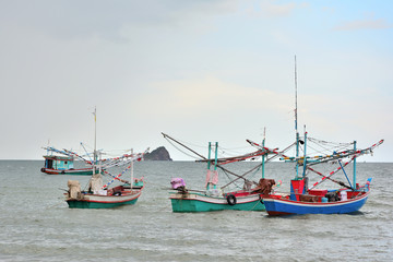 Many fishing boats float on the sea with blue sky background.