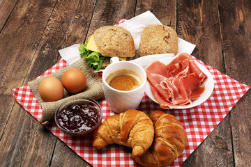 Breakfast On Table With Bread Rolls Croissants Coffe And Eggs