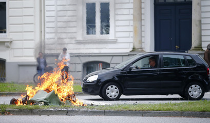 Man drives past a burning garbage bin following a demonstration at the G20 summit in Hamburg