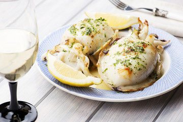 Cuttlefish With garlic, parsley and lemon next to a glass of wine, fork and napkin. Food..