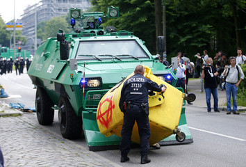 German policeman remove a garbage bin left by protesters in front of a police vehicle during the G20 summit in Hamburg