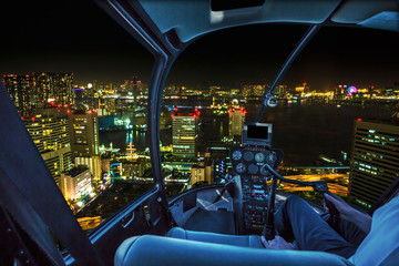 Helicopter flying over Tokyo cityscape, the Bay area with its bridges and Odaiba by night from Tokyo skyline in Japan.