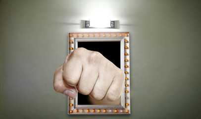 A fist punching out of a lighted picture frame for the concept: provocative artwork.