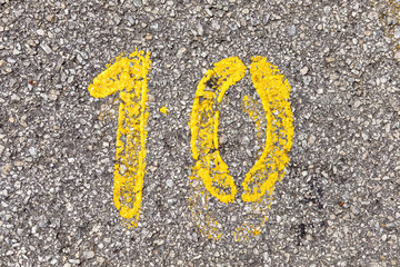 Yellow imprint of the number ten on a tarmac street.