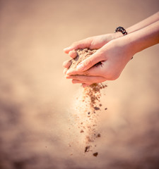 Sea sand falls to the ground through the palm of your hand