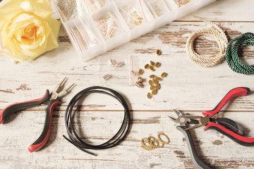 Workspace with tools for making jewelry - pliers, leather, earrings and bracelets, necklace. Kraft tools. Bright rustic wooden desk, table