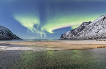 Green lights of Northern Lights (aurora borealis) reflected in the cold sea surrounded by snowy peaks, Ersfjord, Senja, Troms, Norway, Scandinavia, Europe