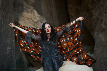 Glamour oriental woman with colorfull shawl on her hands sitting next to a rock