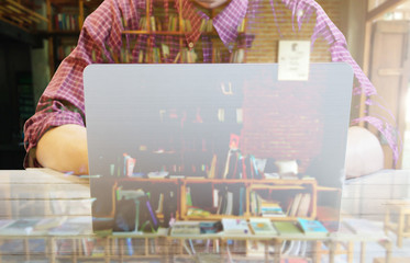 Double exposure of Businessmen use computers and blur library books