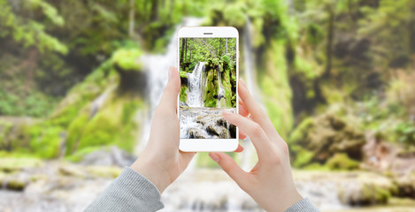 Girl taking photo of waterfall with smartphone in the woods