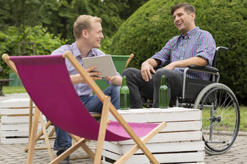 Positive man on wheelchair drinking with friend
