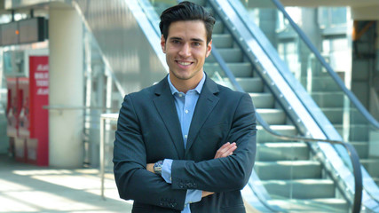 Portrait of a young handsome businessman (student) in a suit, smiling, successful happy, at the station, at the airport. Concept: new business, travel the world, communication, contacts, business deal