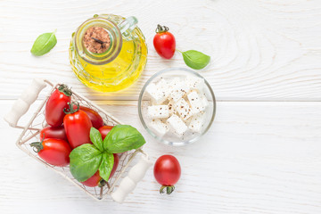 Salad ingredients. Cherry tomatoes, basil, feta cheese and olive oil on white wooden background, top view, copy space