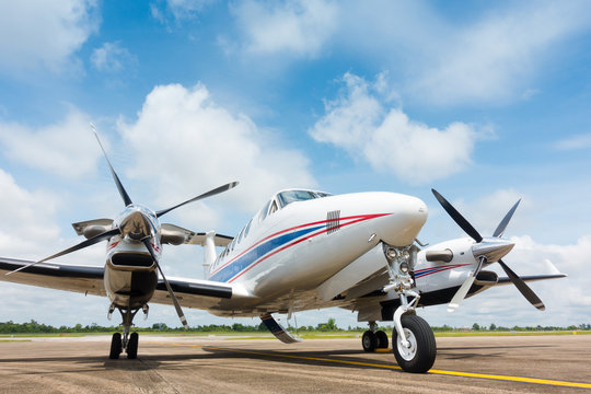 Small Airplane Parked at Airport with beautiful blue sky white clouds background