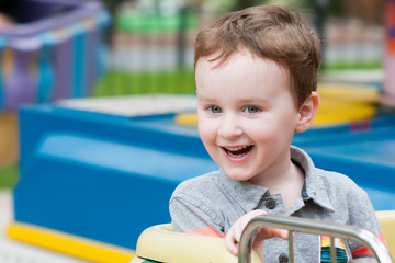 Young toddler boy having fun on boardwalk amusement ride