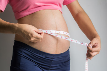 Pregnant woman measuring her belly with tape measure.
