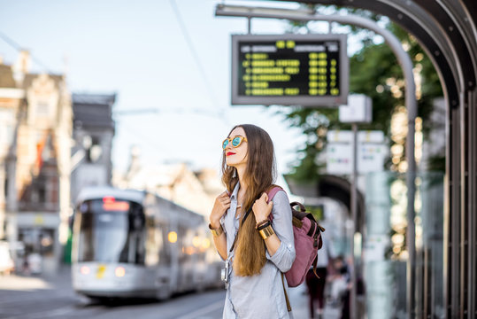 Young woman standing on the tram station with time table in the old town of Gent city in Belgium
