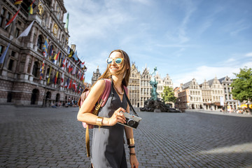 Young woman tourist with photo camera walking on the Great Market square in Antwerpen city in Belgium