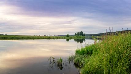 вечерний летний пейзаж на берегу уральской реки с травой, Россия, июль