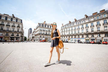 Young woman walking with bag on saint Pierre square with famous Brittany tower on the background in Nantes city in France Fotomurales
