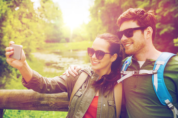 couple with backpacks taking selfie by smartphone