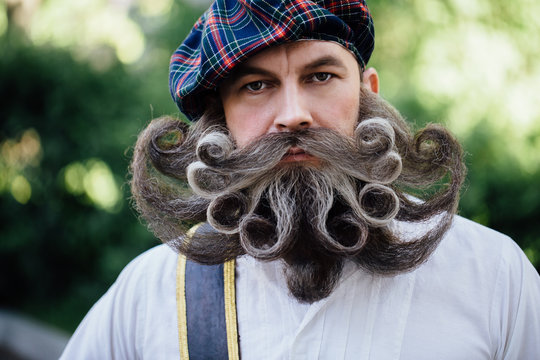 Handsome portrait of a brave Scot with a amazing beard and mustache curls in the Hungarian style.