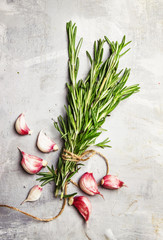 Fresh rosemary and garlic, stone background, top view