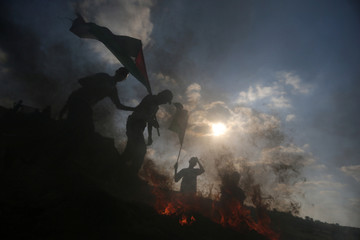 Protesters wave Palestinian flags during clashes with Israeli troops near the border between Israel and Central Gaza Strip