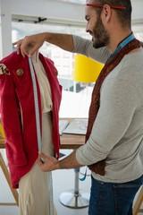 Designer measuring jacket on mannequin