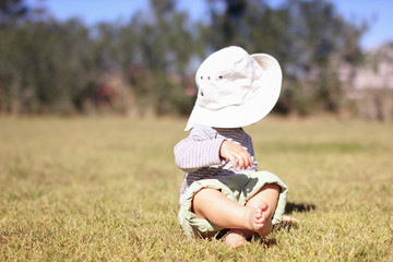 Barefoot baby sitting on the lawn. The kid turned away from the camera. Face hidden under a hat. Copy space for your text