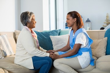Female doctor comforting senior woman in living room