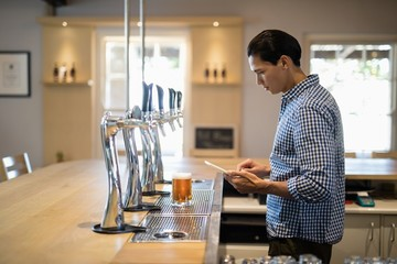 Bar tender using digital tablet at counter