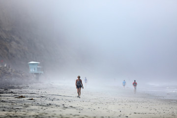 A women finishes off an early morning workout on the beach before a heat wave hits San Diego