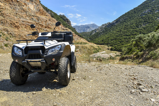 ATV offroad on mountain and sky background.