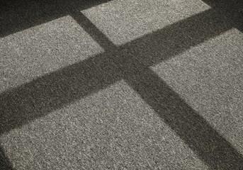 Schatten durch einfallendes Licht auf einem Teppichboden vor einem Fenster