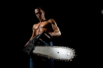 fitness muscular male model with chainsaw