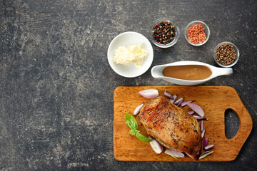 Cutting board with delicious turkey, spices and gravy boat on table