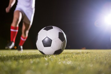 Low section of soccer player and ball on field