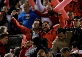 Football fans take a selfie before a match at the Defensores del Chaco stadium in Asuncion