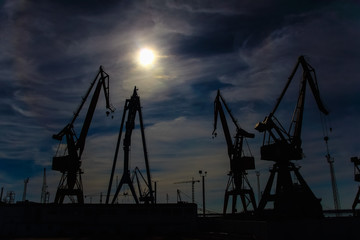 Beautiful landscape of  cranes in shipyard  against a backlight