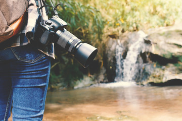 Women holding camera and waterfall background, concept travel on holiday