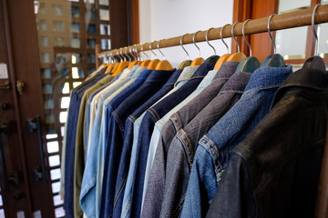 Lot of different fashion jeans jacket on hangers