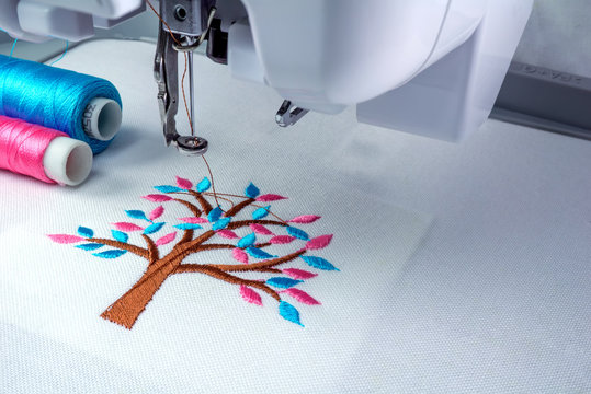 Close up picture workspace of  embroidery machine show embroider tree design theme. And two thraed s cyan and pink color.