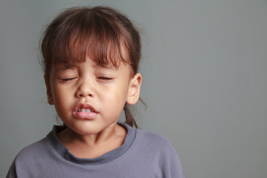 Girl child sneezing on a gray background.