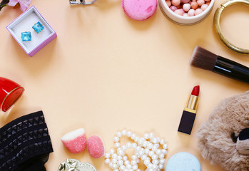 Cosmetics, decorations, sweets on a beige background