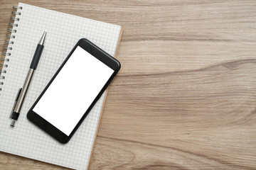 Mockup with smartphone and notebook on desk. Top view with copy space.