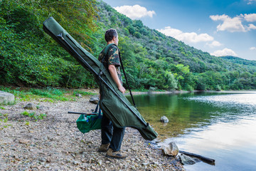 Foto op Plexiglas Vissen Fishing adventures, carp fishing. Fisherman on a lake shore with camouflage fishing gear, green bag and mimetic rod holdall